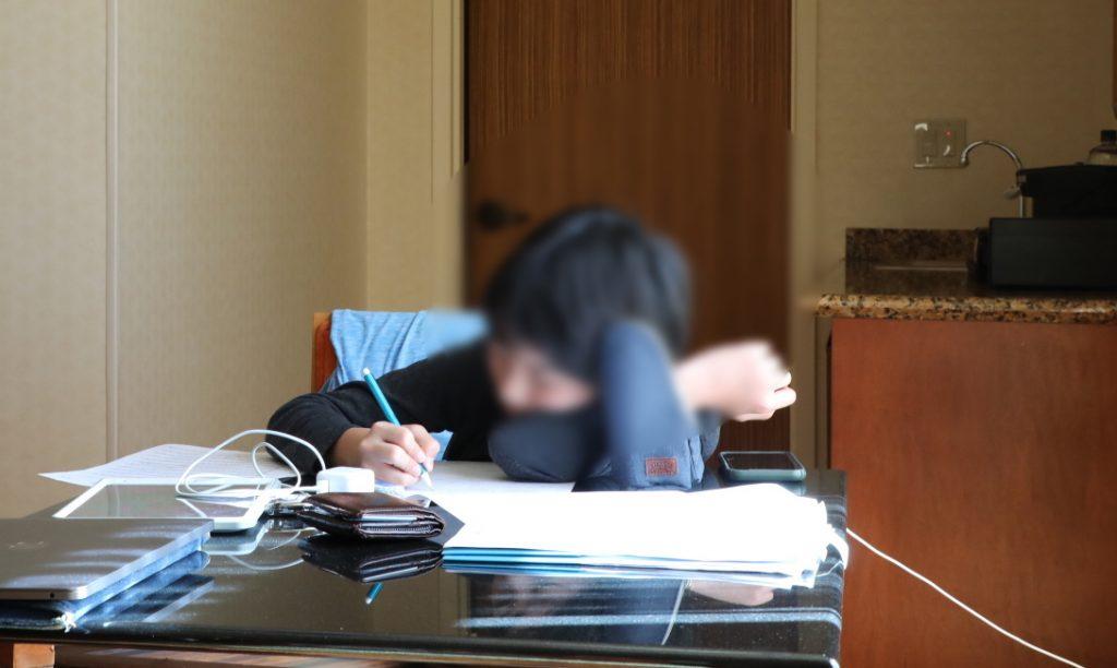 旅行先のホテルで勉強する次男